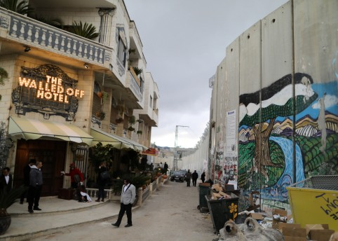 People stand outside the Walled Off hotel, which was opened by street artist Banksy, in the West Bank city of Bethlehem March 3, 2017.