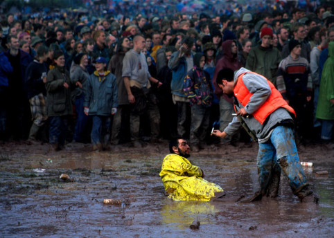 A festival-goer defeated by the mud, 1990s © Ann Cook